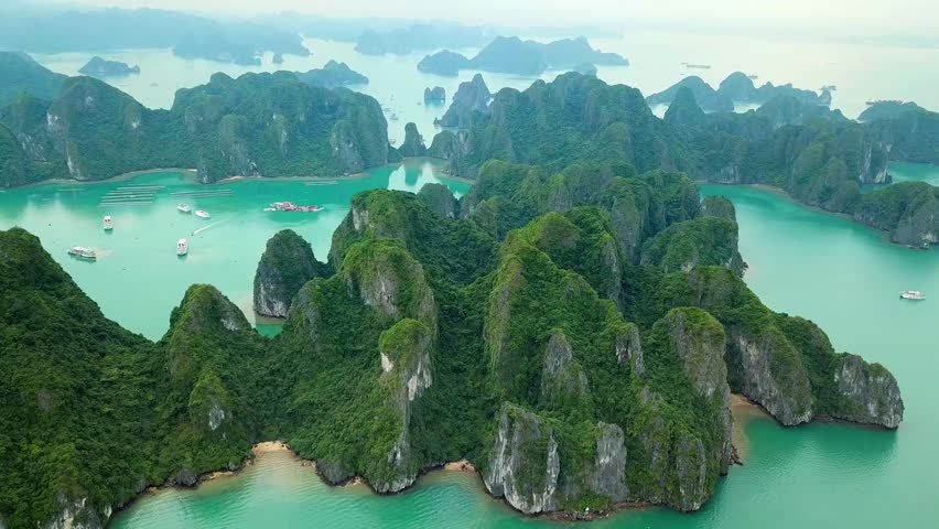 Unique aerial drone flight over natural rocks green tops Halong bay islands from sea blue azure water. Wild natural untouched seascape. Asia Vietnam. Best Travel sight.  | Shutterstock HD Video #1027431254