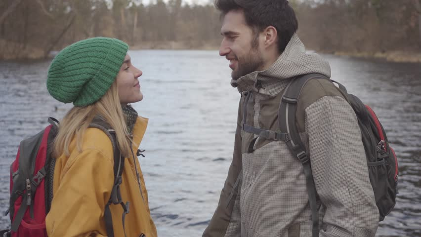 Portrait of the young couple of tourists standing on the river bank with backpacks on their backs. Bearded man and pretty woman in yellow jacket talking and smiling. Lovers rest outdoors. Side view