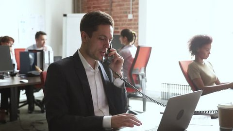 Male broker sales manager worker in suit talking on the phone using laptop at work desk, serious businessman employee making telephone call consulting customer in modern office at corporate workplace