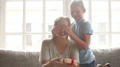 Cute kid daughter covering mum eyes making surprise to happy young mom, child girl hugging excited mommy congratulating with mothers day concept presenting gift box embracing sitting on sofa at home