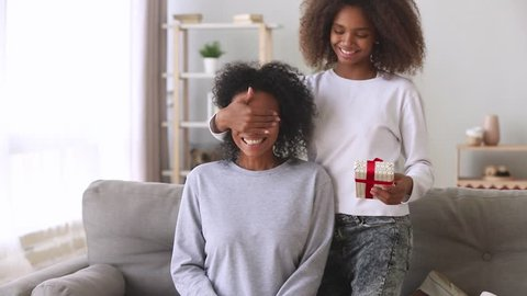 Mothers day present concept, african american teen daughter make surprise congratulating happy excited black mommy closing mum eyes embracing mixed race mom giving gift box hugging on couch at home