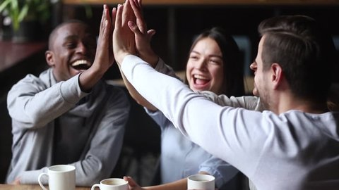 Diverse young happy friends join hands giving high five together celebrating multicultural friendship at reunion cafe meeting, multiracial mates students team bonding engaged in unity support concept