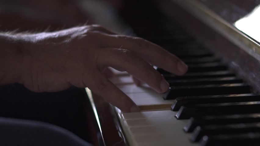 Musician plays piano, in Slow Motion video, in a room with natural light #1027528754