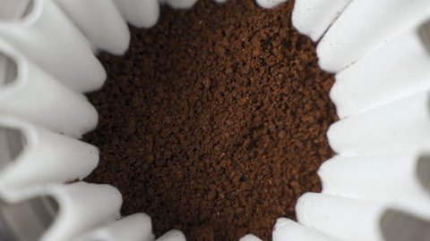 Hot water pour over into ground coffee beans close up slow motion