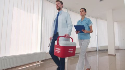 Medical courier with an assistant go down the clinic hall with red human organ trafficking container | Human organ transplantation concept