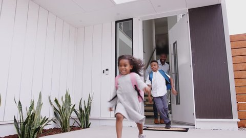 African American Excited Children Running Out Of Front Door On Way To School Watched By Father