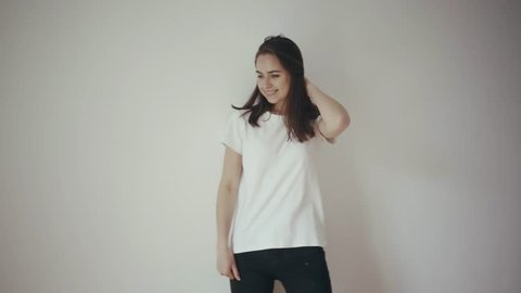 Young beautiful girl posing in front of the camera in white cotton blank t-shirt and black jeans with white isolated wall on the background, mock up of clothes, happy smiling and laughing