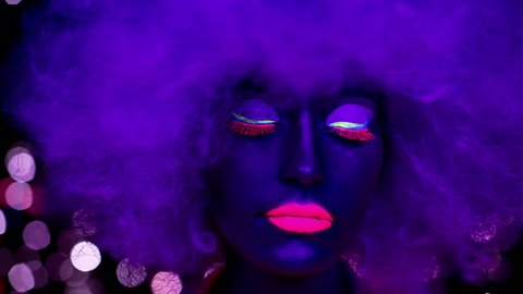 sexy cyber raver woman with large afro wig filmed in fluorescent clothing under UV black light