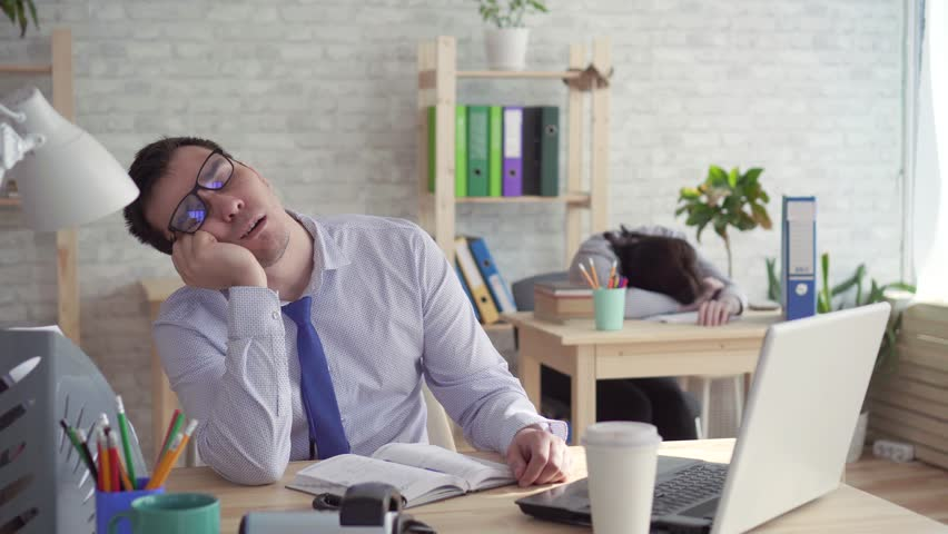 Sleepy workers in the office,a man and a woman sleeping at work, answering the phone