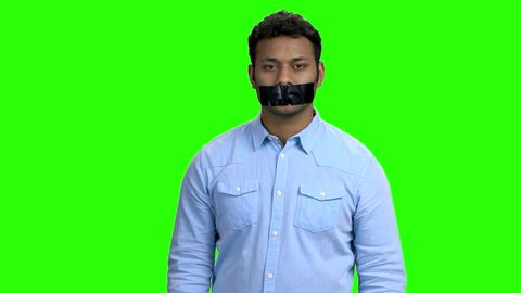 Indian man with taped mouth on green screen. Portrait of young attractive man with mouth and lips sealed with adhesive tape. Censorship in expression of ideas.