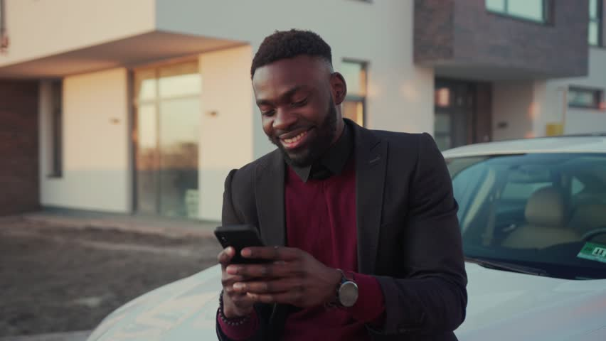 Charming smiling young african american man stand speak by phone in city near white car happy technology businessmen busy people attractive modern lifestyle smartphone ambitious mobile slow motion | Shutterstock HD Video #1027674224