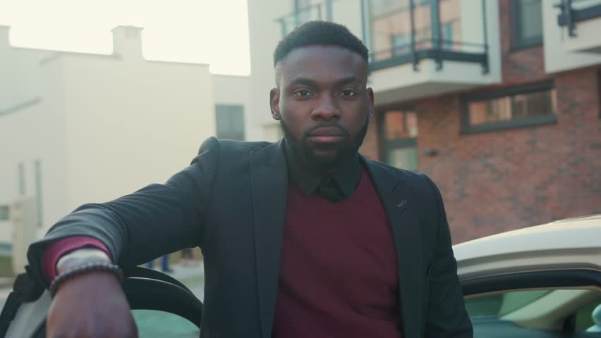 Handsome african american man stand near white car look at camera sunset young vehicle open passenger arm auto street automobile businessman buy jacket portrait close up slow motion | Shutterstock HD Video #1027674344