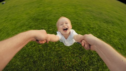 Dad hands holding spinning little happy smiling cute son playing together at nature countryside POV shot carefree family enjoying weekend relaxing having good time outdoor high angle
