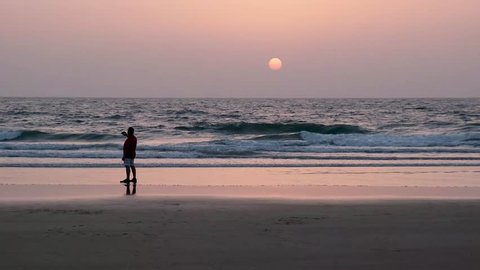 A man taking picture on the phone of dramatic sunset on the beach In India