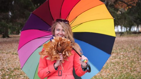 Happy longhaired blonde girl with a large colourful umbrella in a red coat in the autumn park turns around and smiles at the camera with yellow maple leaves in her hand.