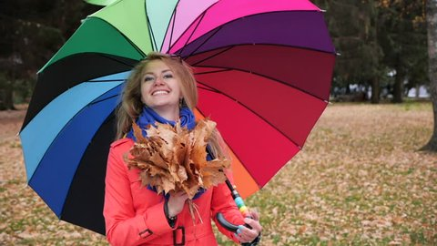 A young cute longhaired blonde girl with a large colourful umbrella in a red coat in the autumn park turns around and smiles at the camera holding a bouquet of yellow maple leaves. Slow motion.