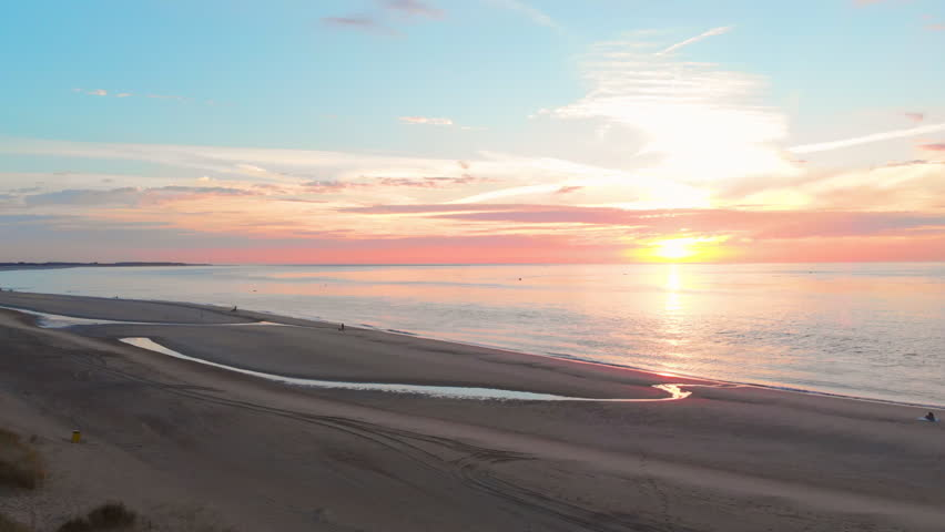 A calm low tide at the beach near the Stormsurge barrier in the south west of the Netherlands, during sunset. Smooth dynamic aerial shots on the beach. Right to left, medium height, towards the dunes.   Shutterstock HD Video #1027759934