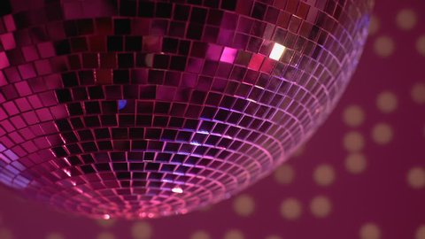 Mirror disco ball rotating in nightclub lights, festive party atmosphere, fun