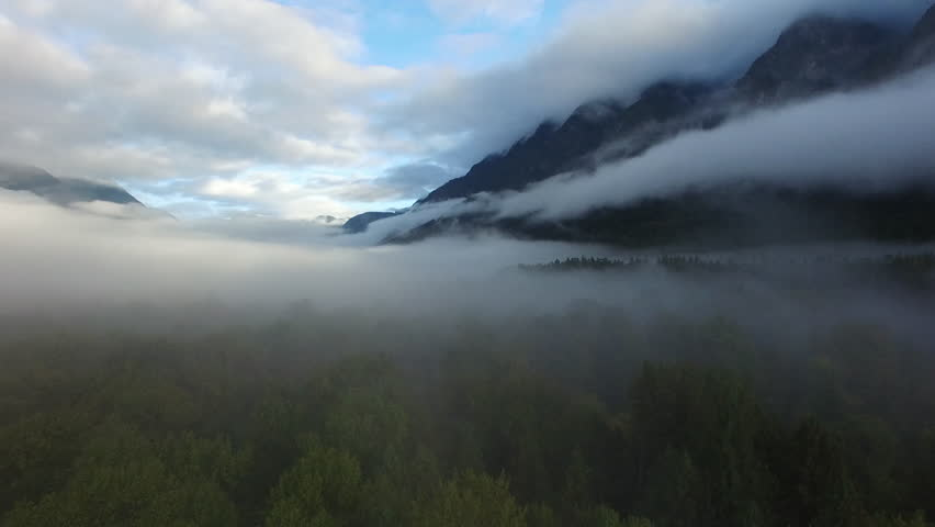 Aerial: Thick Fog Covering Forest and Mountains, Blue Sky In Background in Bella Coola, British Columbia | Shutterstock HD Video #1027874714