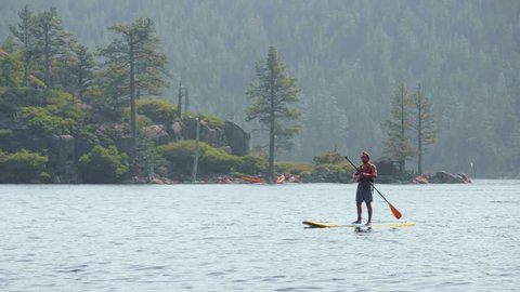 Stand Up Paddleboarder in Emerald Bay Lake Tahoe Tracking Shot
