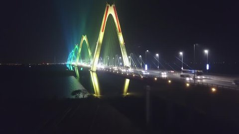 Night colorful neon illumination Nhat Tan Cable-stayed bridge crossing Red River. Hanoi Vietnam. Close Pillars Road traffic cars Six-lane highway. Modern architecture of city. Rise above Drone