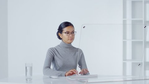 Lockdown of young Asian woman in eyeglasses sitting in office at invisible multi-touch screen and typing on wireless keyboard. Suitable for adding AR graphics