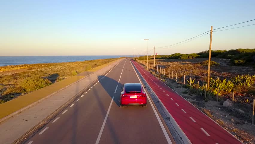 Aerial, drone shot, following a red,suv, electric, sports car, driving on Guincho road, at the atlantic sea, towards a lighthouse, at a sunny evening sunset, in Cabo Raso, Carcais, Portugal | Shutterstock HD Video #1027921544