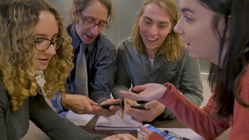 College or University professor leading a discussion with his students while looking at his mobile phone in a classroom in slow motion | Shutterstock HD Video #1027950524
