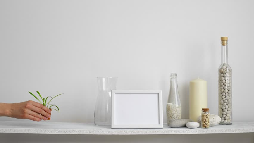 Modern room decoration with picture frame mockup. Shelf against white wall with decorative candle, glass and rocks. Hand putting down potted spider plant.  | Shutterstock HD Video #1027969454