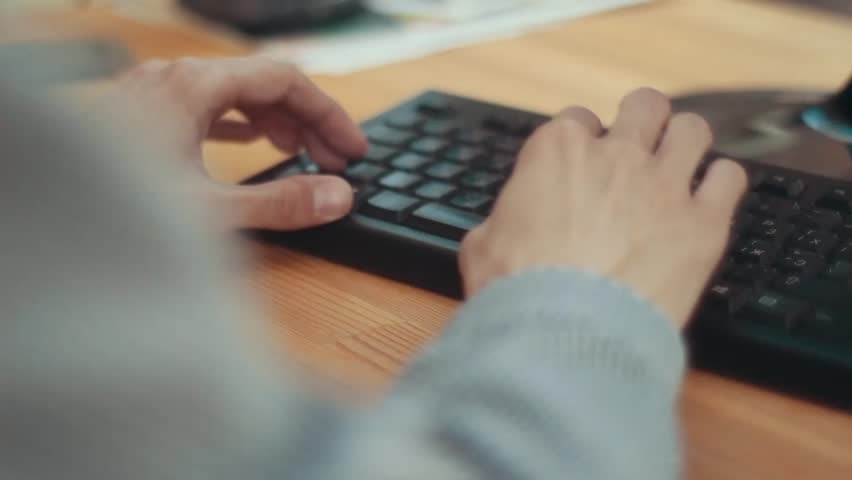 Male hands are typing on the keyboard. Wooden table. | Shutterstock HD Video #1027982084