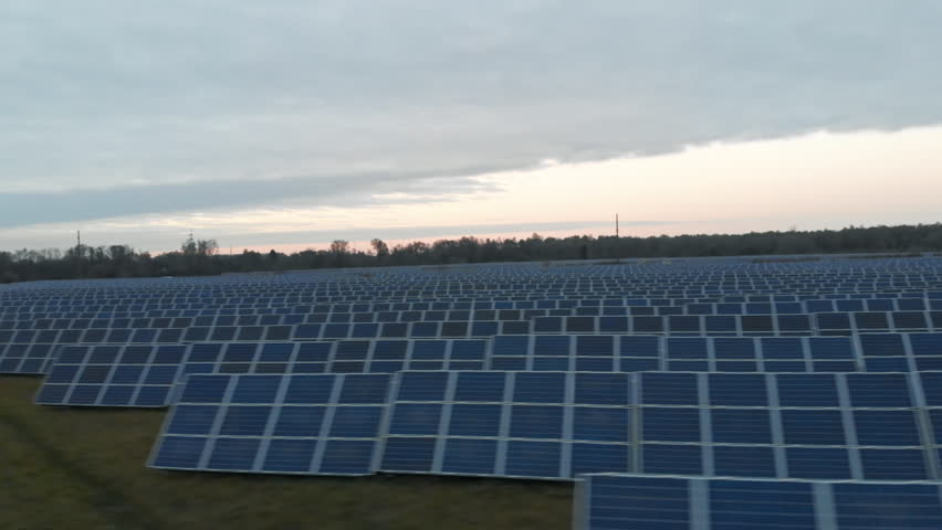 Top aerial view of the solar power plant under cloudy sky in summer. Large solar batteries on the field.