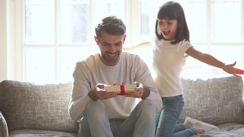 Cute kid daughter make surprise present covering eyes of happy dad receive gift box sit on sofa, little child girl congratulating parent smiling excited daddy on fathers day birthday embrace at home