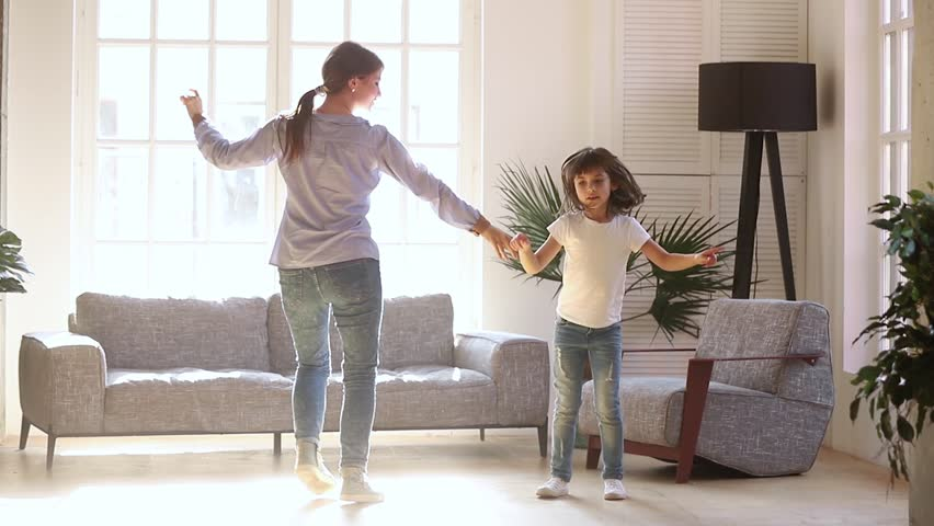 Active young mom babysiter and cute little kid daughter jumping dancing in modern house living room, happy family mother with child girl having fun enjoy playing funny activity together at home | Shutterstock HD Video #1028009684