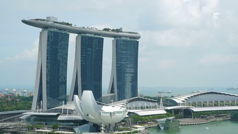 Stunning time lapse of the amazing Marina Sands Hotel in amazing Singapore City with boats cruising across the bay.