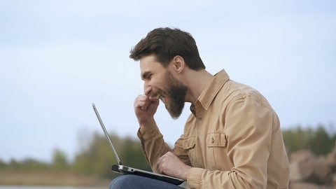Portrait od beard man freelancing outdoors. Looking at the laptop, see good news. Positive, victory emotions and hapiness.