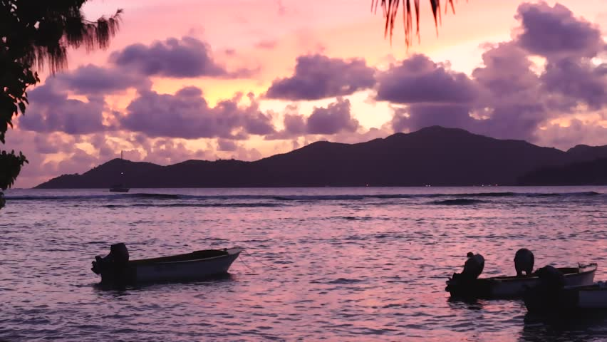 Silhouette of small boats floating in the waves in front of a nice sunset on La Digue, Seychelles. #1028017094