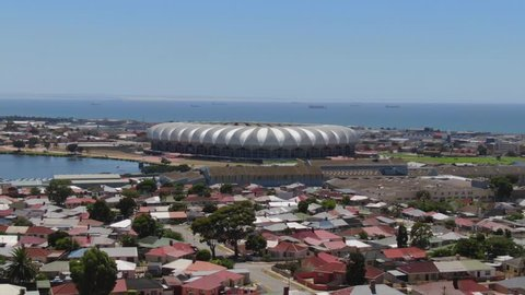 Port Elizabeth, South Africa - circa 2010s: Nelson Mandela Bay Stadium. Wide aerial view fly forward and rise up reveal ships at sea and industrial buildings and traffic surrounding stadium, sunny day