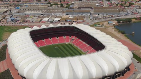 Port Elizabeth, South Africa - circa 2010s: Aerial orbit of Nelson Mandela Bay Stadium. Close view of stadium, see seats and soccer field with industrial area and North End Lake in background