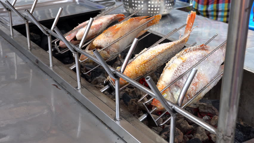 Are very popular among tourists Salt-Crusted Thai Grilled Fish: Pla Phai Kleua. Asian street Food. People cooking, selling and buying Exotic Asian Thai food