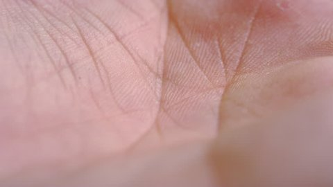 Macro close-up of a single blue ibuprofen liquid gel pill dropping into a human hand