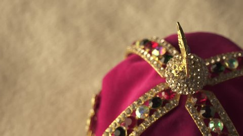 Extreme macro close up shifting focus at gold and jewel diamond King's crown on the white soft pillow. Slow rotation motion. 4k, uhd.