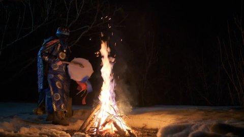 The shaman is dancing a ritual dance near the fire.