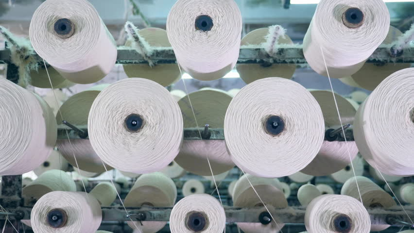 Spinning clews with threads on a rack at a textile plant. | Shutterstock HD Video #1028132744