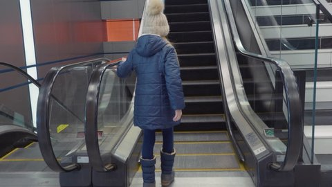Little girl goes up the escalator. The girl independently rises upstairs on a moving escalator. Back view