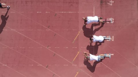Aerial view over a three sprinter athletes sprinting away from the start line