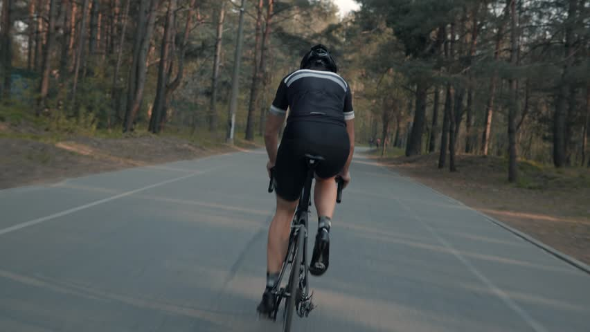 Cyclist Riding On Road Bike Rear View.Cycling Men Pedalling Road Bicycle On Park.Tracking Shot Of Triathlete Rides On Road Bike At Sunset.Cyclist Athlete Intensive Training On Bicycle.Sport Concept.