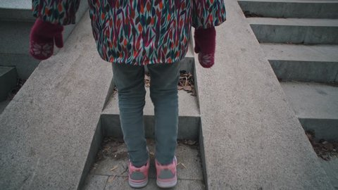 View back handheld shoot of little girl in pink sneakers climbs stone steps in dry leaves. Child walks on gray stairways in city park.