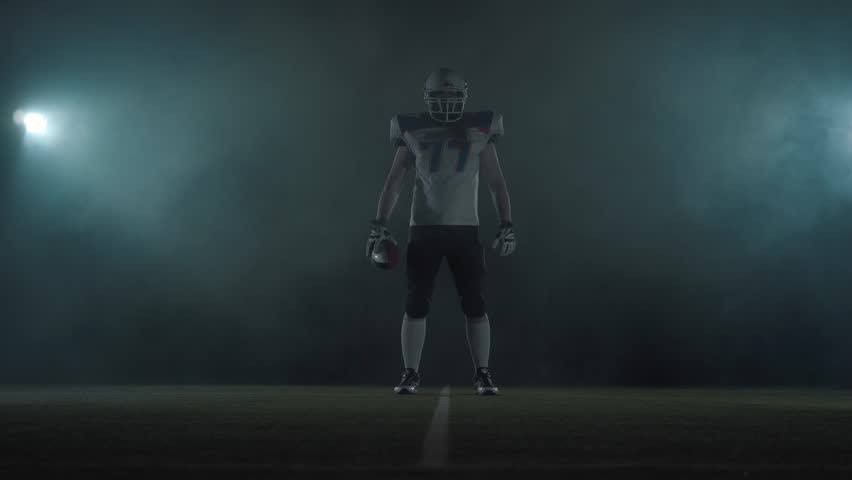 American football sportsman player in football helmet standing on the field on black background in a cloud of smoke with the ball in hands. The man raising ball makes making threatening gestures | Shutterstock HD Video #1028326874