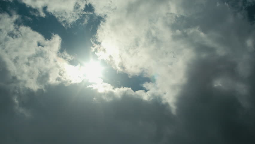 Wide shot looking up at the sun shining and casting a lens flare in a blue sky as a fluffy white cloud approaches | Shutterstock HD Video #1028344064