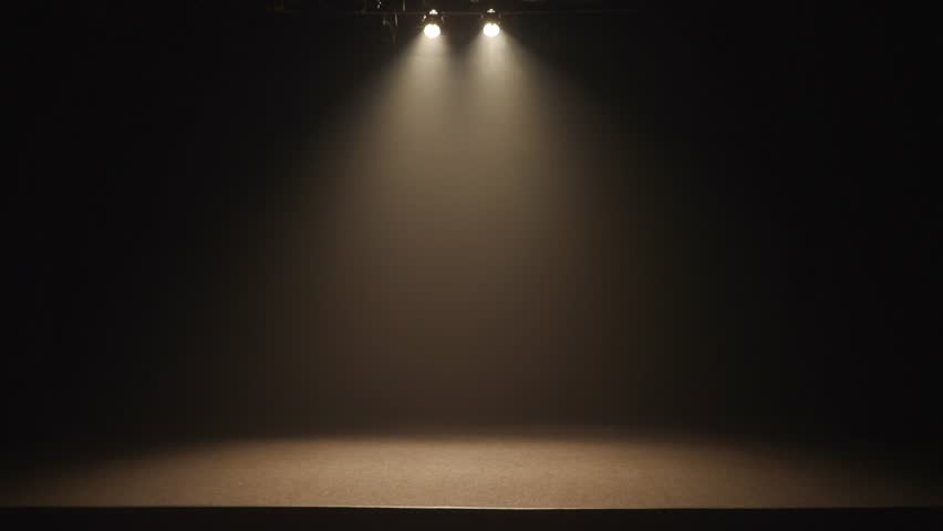 The stage of a small theater with white spotlights. Lights are turned on from darkness.